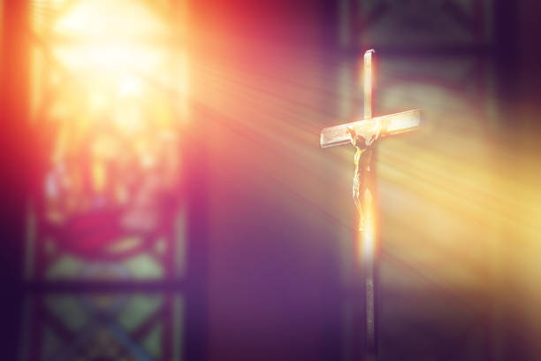 crucifix, jesus on the cross in church with ray of light from stained glass stock photo