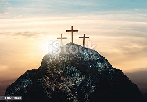 istock Crucifixion of Jesus Christ, three crosses on hill 1140793998