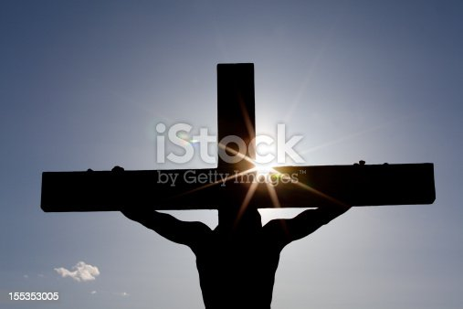 A silhouette of Christ on the cross. Easter theme. Horizontal colour image. Sunset. Flare. This image of the crucifixion is a powerful statement of Jesus and his love for mankind. The redemptive power of the cross is the central theme of Christianity and the Christian religion.