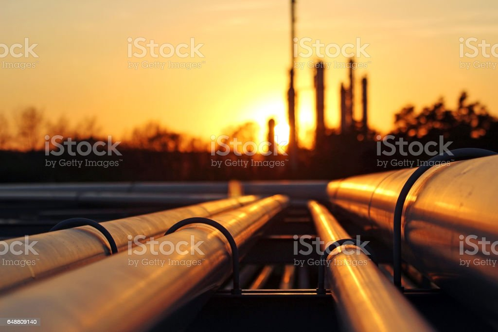 crude oil refinery during sunset with pipeline conection stock photo