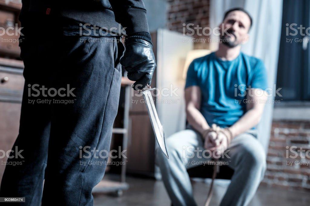 Criminoso cruel, segurando uma faca na mão - foto de acervo