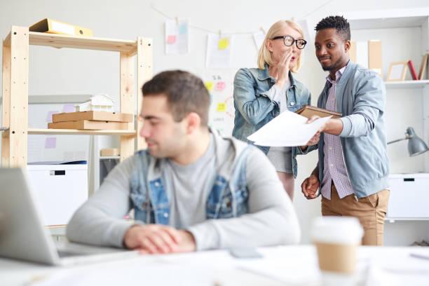 Grausame multiethnischen Bürokollegen diskutieren neue Mitarbeiterin: Frau mit blonden Haaren flüsterte Kollegen ins Ohr während er zeigte auf den Mann am Tisch sitzen – Foto