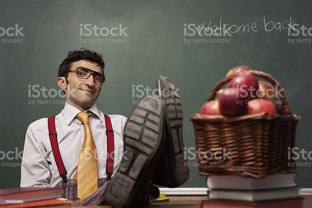 Cruel teacher sitting and teaching stock photo