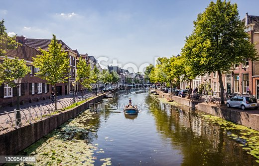 Leiden, the Netherlands - June 27, 2018: Small boat with tourists on a canal in city center of beautiful Leiden, Holland in Summer. Dutch old buildings facade view.