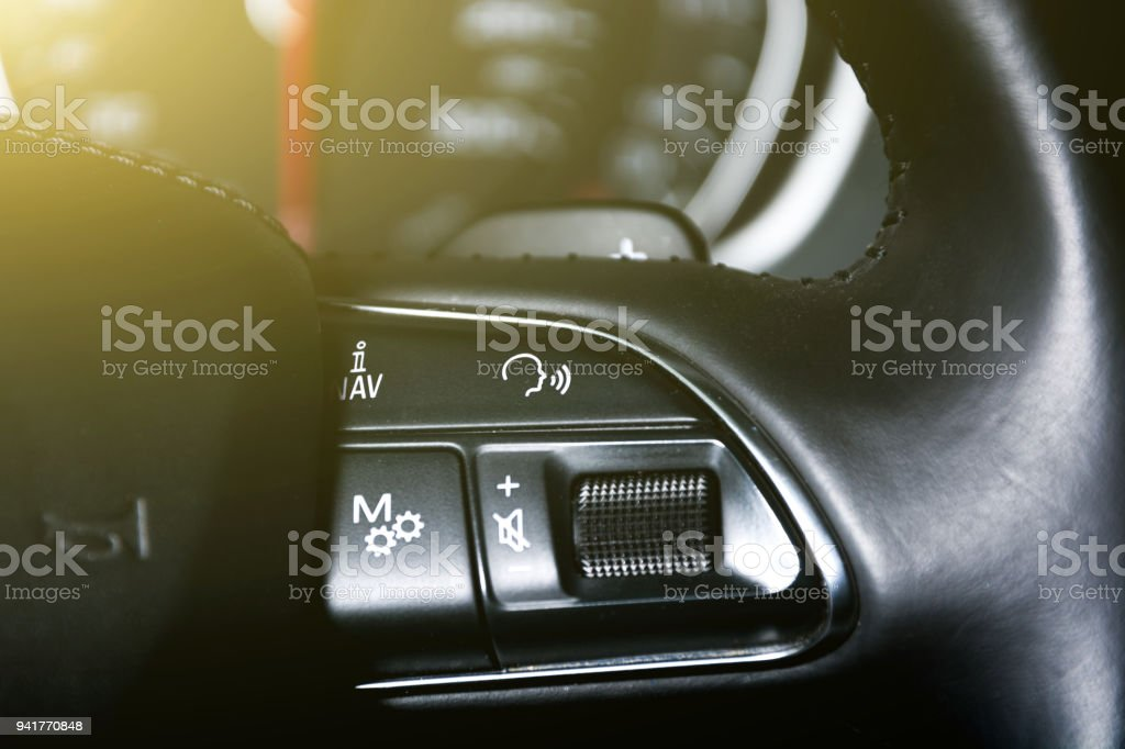 Cruise control and speed limiter buttons on the car steering wheel stock photo