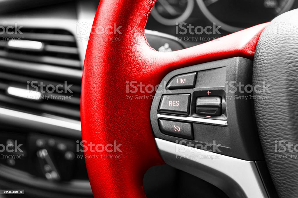 Cruise control buttons on the red steering wheel of a modern car, car interior details stock photo