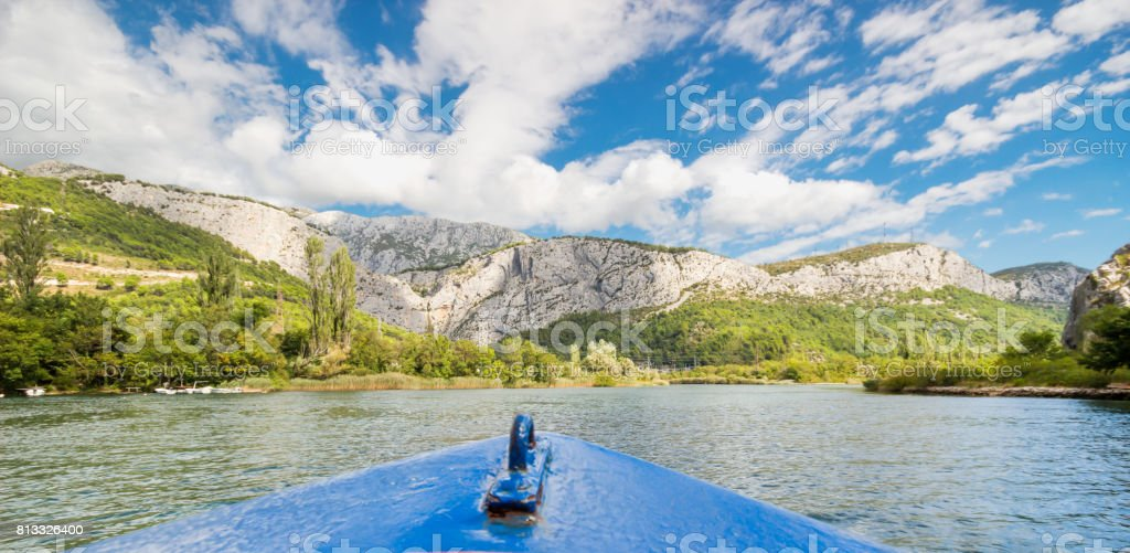 Cruise in the Cetina river inn Omis, Dalmatia, Croatia with mountain, sky and cloud background. stock photo