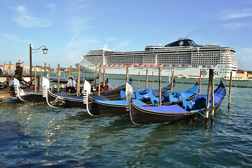 Cruise liner is leaving the Venice lagoon in a sunny Easter spring day and a gondoliere waiting for passengers at the pier with gondolas attached to wooden poles.