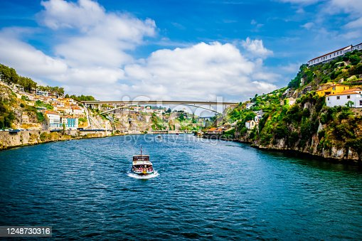 A boat full of tourists on the Douro river in Porto during a sunny day of summer.