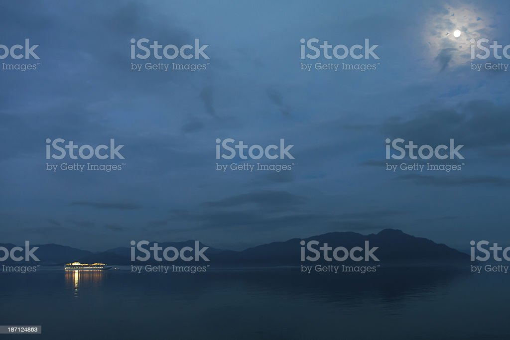 Cruise ship approaches Glacier National Park under full moon royalty-free stock photo