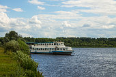 cruise ship at the Bank of the Volga river with green grass and trees on the horizon on a cloudy summer day and space for copying in Tver region
