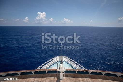 A view overlooking the bow of a cruise ship in clear, blue waters.