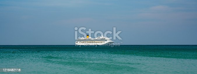 A Cruise ship seen in the middle of the Andaman Ocean near Patong Beach in Phuket, Thailand, during a hot summer day in the tropics.