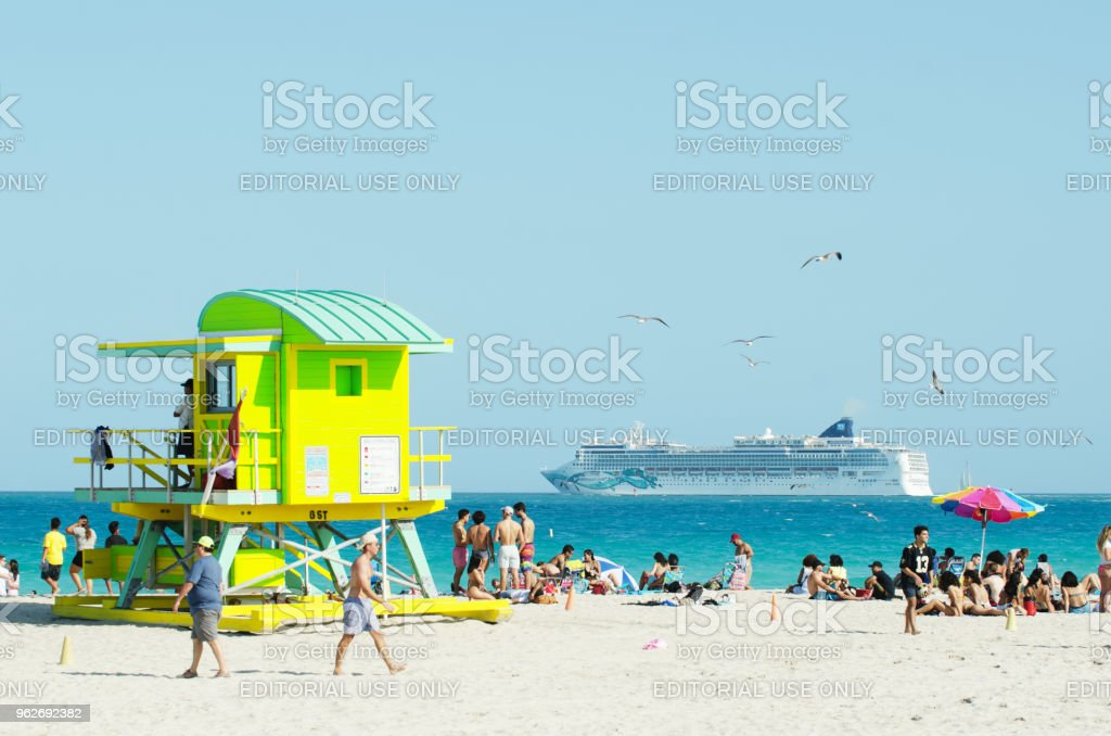 Cruise Ship Leaving Port Miami Florida Miami - April 14, 2018: Groups of young people play games and socialize on South Beach as a cruise ship leaves port on the horizon. Adult Stock Photo