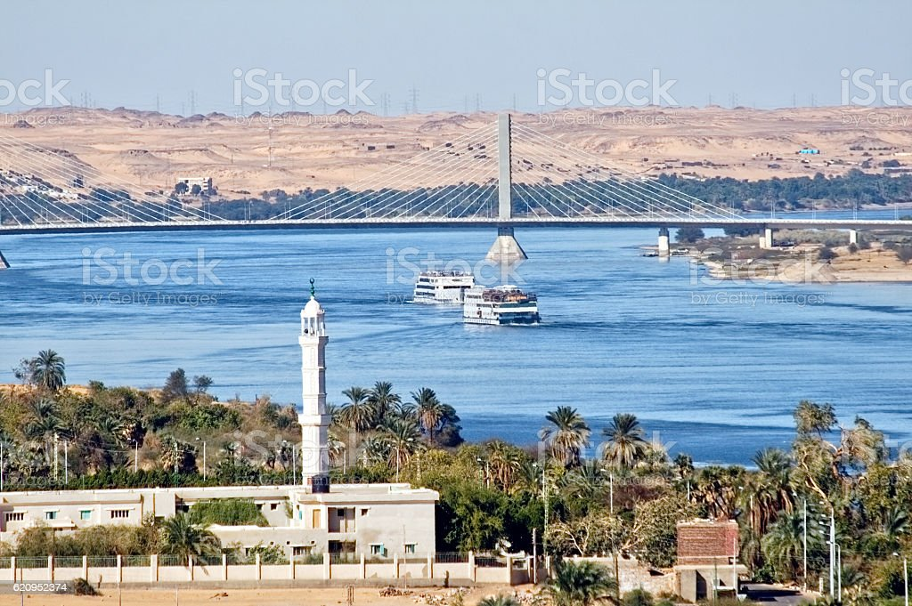 Cruise ship on Nile River with mosque in foreground. stock photo