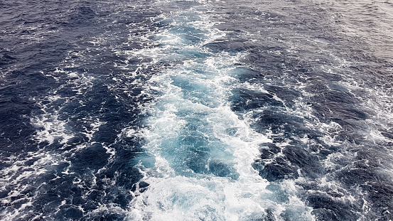 Cruise ship or trail on the surface of the blue red sea. Sea water ship trail with white foamy wave. Top view of the deep ocean. Perspective of a wave of white water