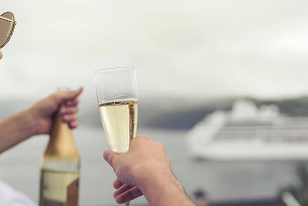 cruise ship passing by, champagne in hand stock photo