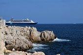 Nice, France - July 6 2019: cruise ship passing a rocky coastline seaside scenery
