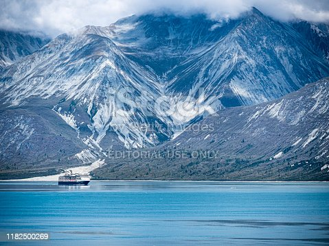 Telephoto view of Holland America Line cruise ship sailing through Alaska's Glacier Bay National Park in late summer.