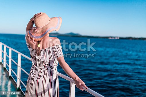 Rear view of young woman on ship deck looking at horizon over sea. Summer vacation and travel concept.