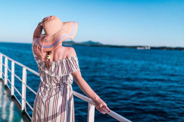 Crucero mujer de vacaciones disfrutando de vacaciones de viaje en el mar. Chica feliz despreocupada libre mirando al océano y sosteniendo el sombrero de sol. - foto de stock