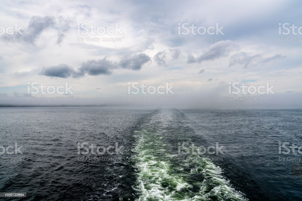 Cruise ship wake trail against hazy horizon with clouds. stock photo