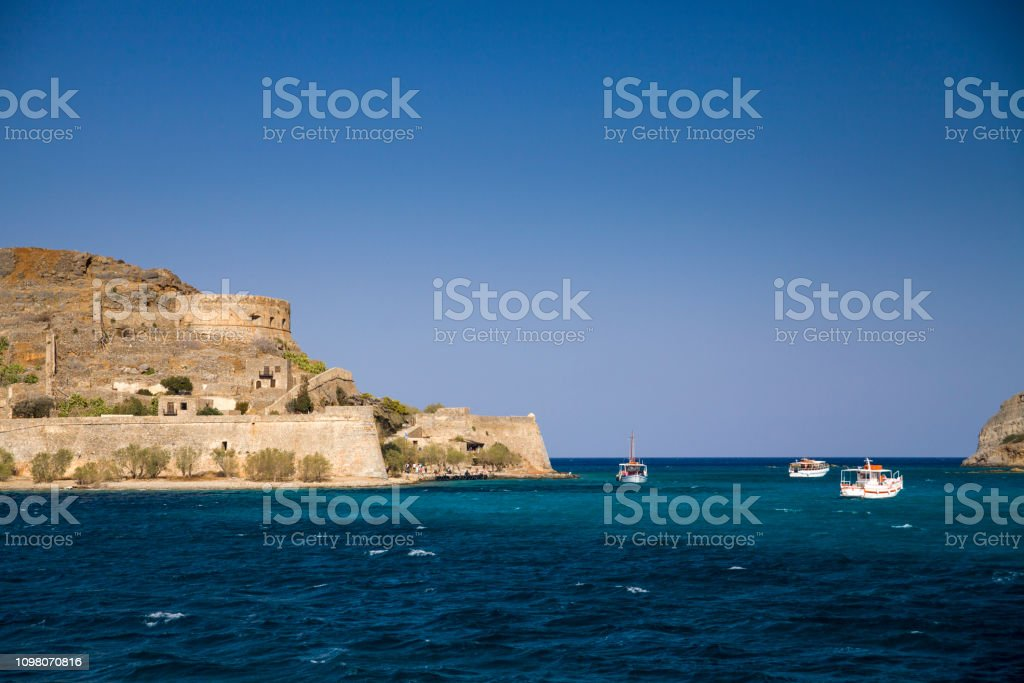 Cruise to the island of Spinalonga. Small boat on the blue lagoon. Spinalonga fortress on the island of Crete, Greece. Architecture on the island. – zdjęcie