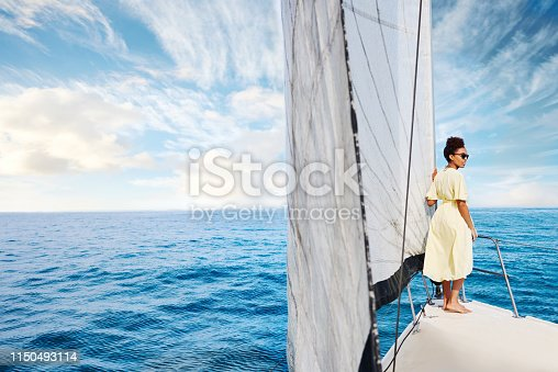 Shot of a young woman enjoying a relaxing day on a yacht