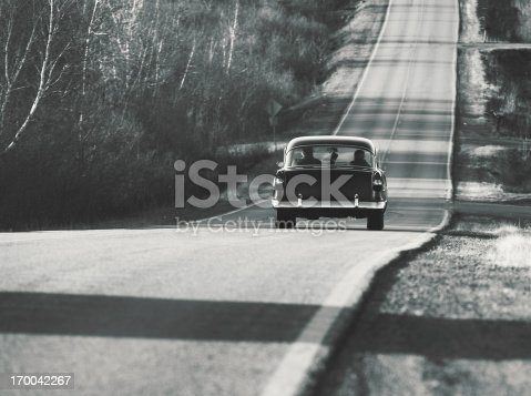A senior couple enjoys a Spring drive in their 1950's coupe.  Toned black and white.