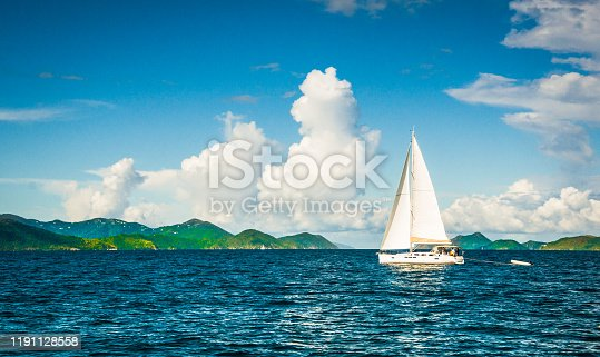 A single white sailboat cruises through the beautiful Caribbean waters off the island of Tortola under fair weather clouds.