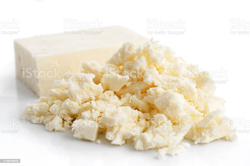 Crumbled white feta cheese isolated on white. stock photo
