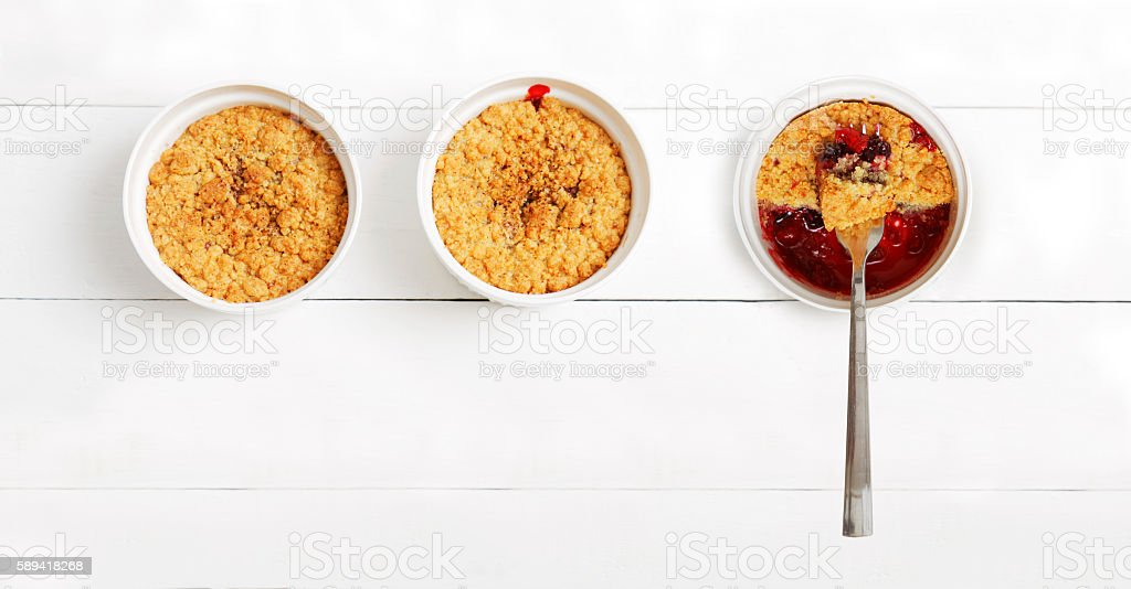 Crumbles with raspberries, gooseberries and blackberries stock photo