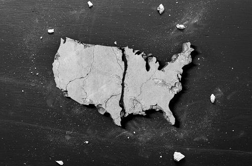 Crumbling Shape of America - Do to coronavirus quarantine the USA economy and housing market crumbling concept on black background.