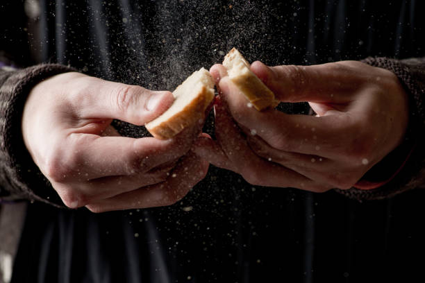 crumbs fly away, hands break crouton in half stock photo