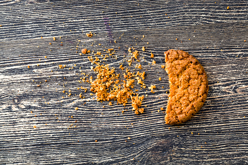 crumbled into a large number of crumbs oatmeal cookies, fresh and bake homemade, sweets on the table, close up