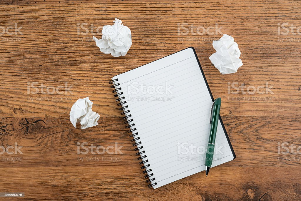 crumple paper and pen with notebook on the desk stock photo
