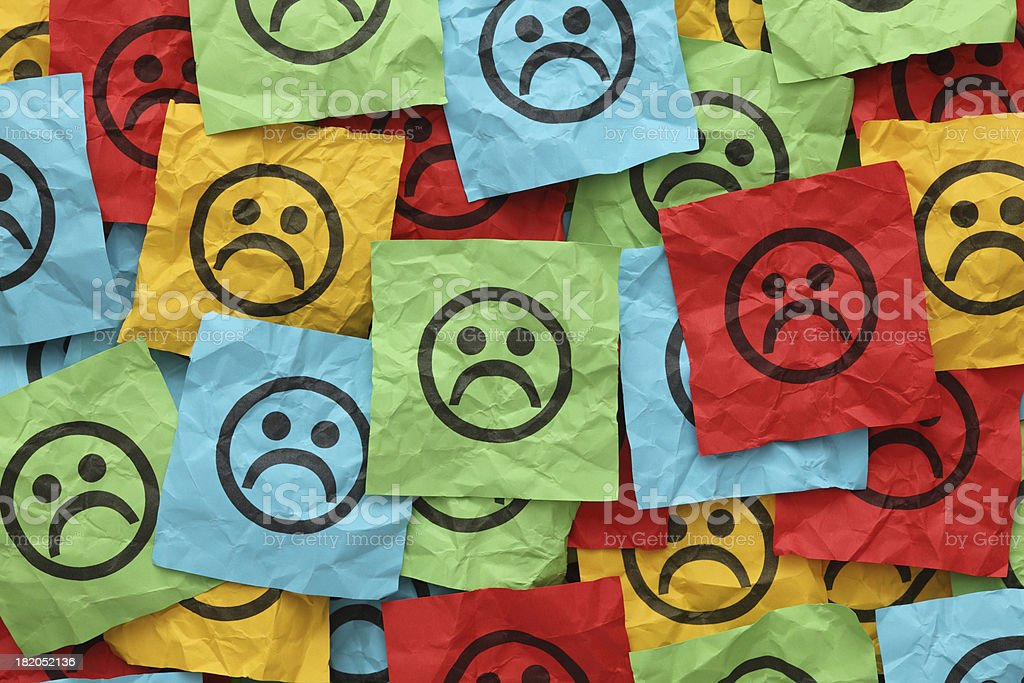 Crumpled adhesive notes with sad faces stock photo