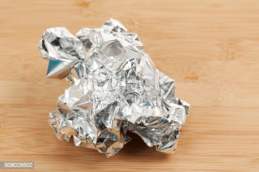 Aluminum Foil Ball. Crumpled aluminum foil ball on a wooden surface.  Shot in studio with Canon 5D Mark II DSLR camera.