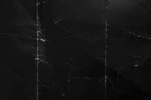Crumpled black cardboard with wrinkles and wrinkled folds. Old wrapping dusty paper. Abstract dramatic background. For design and titles.