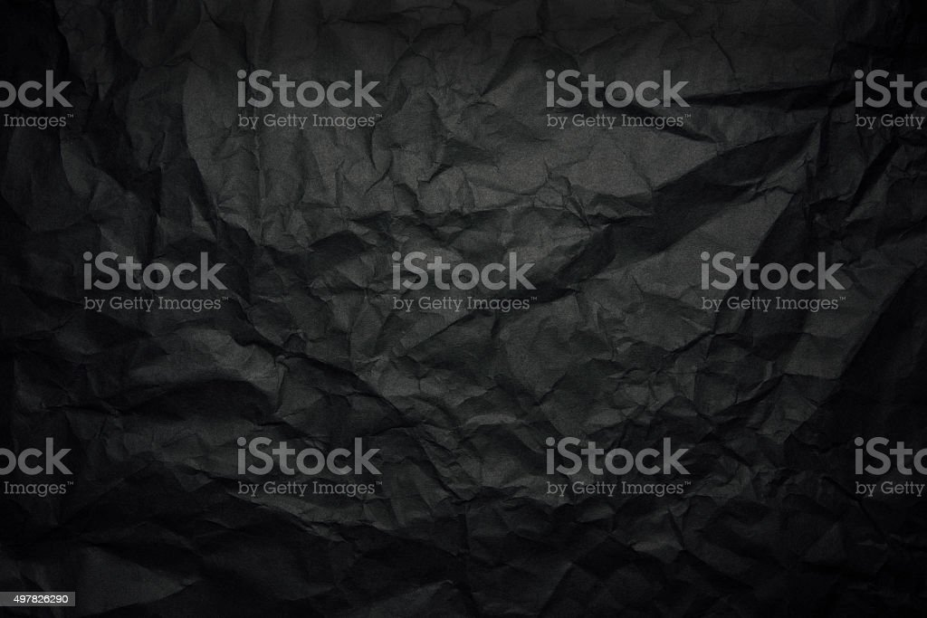 Crumpled black rice paper background with spotlight stock photo