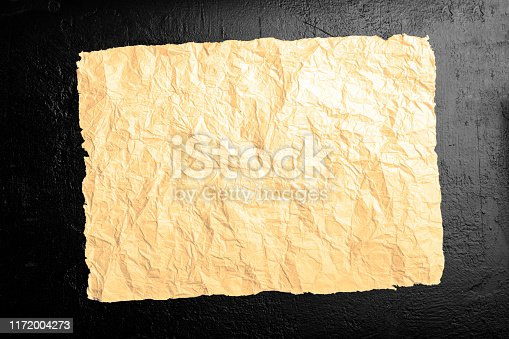 891131294istockphoto Crumpled brown page on a black background 1172004273