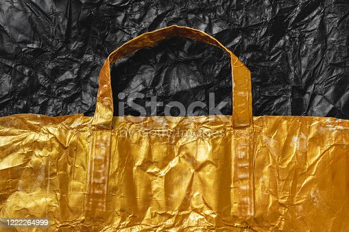 Crumpled gold shopping bag background.