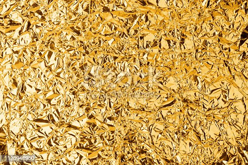 Crumpled golden foil shining texture background, bright shiny gold luxury design, metallic glitter surface, holiday decoration backdrop concept, gold metal shimmer effect, sparkling yellow pattern