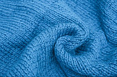 Crumpled knitted blue fabric background, waved and twisted, curved turquoise woolen knitwear.