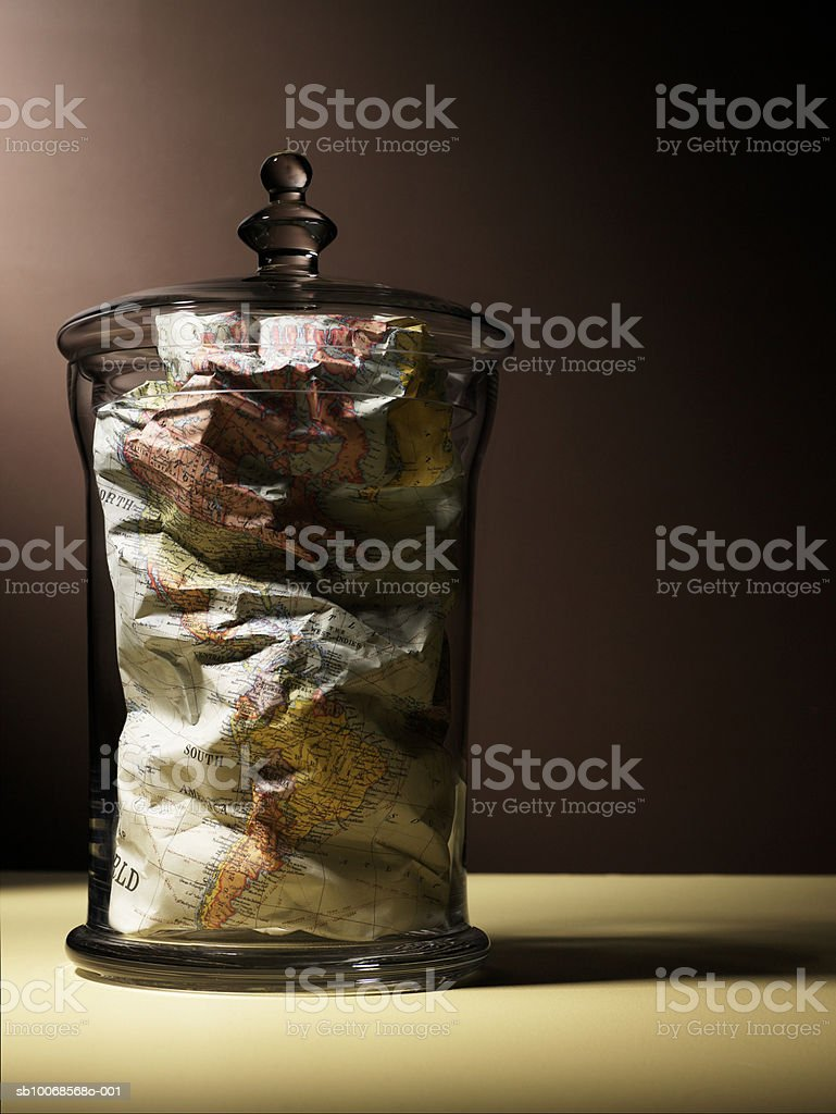 Crumpled map in glass jar, close-up royalty-free stock photo