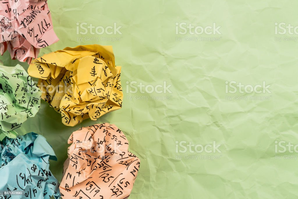 crumpled multi colored paper ball with mathematical equations on