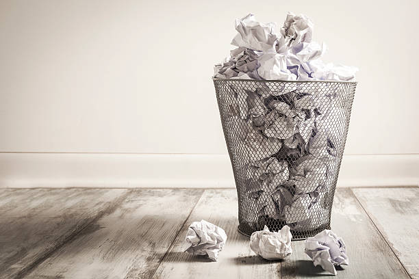 Crumpled paper in the trash can stock photo