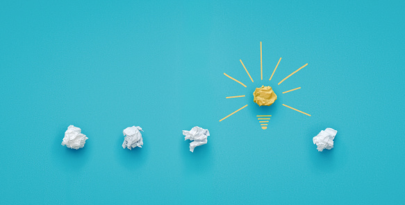 istock Crumpled paper light bulb over blue background 1130146931