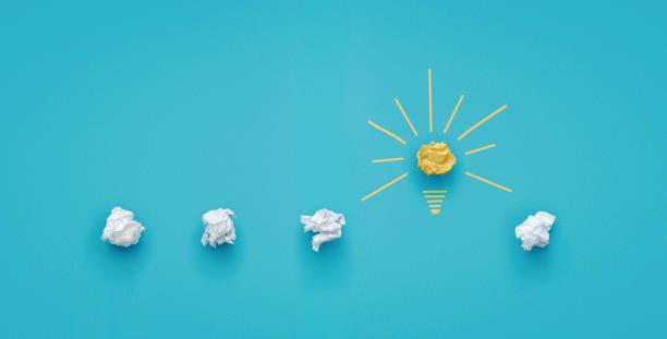 青い背景に紙を丸めて電球 - 機会 ストックフォトと画像