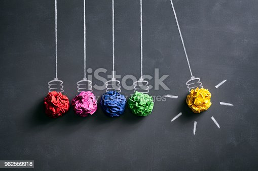 Conceptual photography of colored crumpled paper on a smudged blackboard.